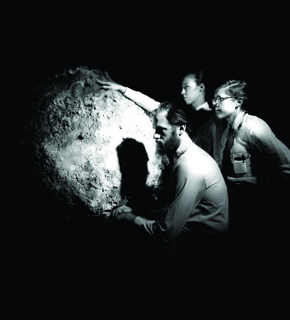 Officials of North American Aviation, Inc. study a replica of the moon shortly after the announcement that NASA had selected NAA as prime contractor for the Apollo command and service modules. Pictured (clockwise): Sarah Belknap, Marissa Lee Benedict, Joseph Belknap. Photo credit: Jeff Austin.