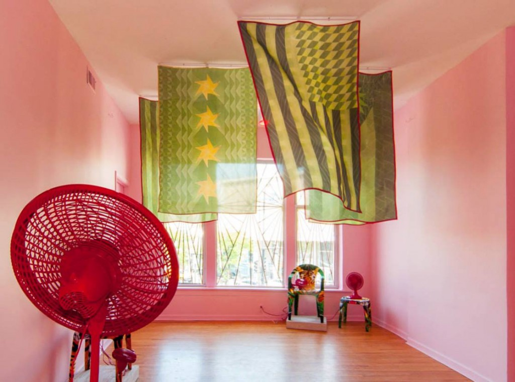 "Edra Soto. ""Say Everything,"" 2014, installation view at The Lloyd Dobler Gallery mixed Media (flags, fans, plastic chairs, beach towels, tape, sand, cooler, pink light, latex paint). Photo by Michael Soto"