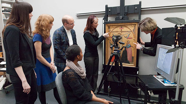 """Art history graduate students from the University of Chicago and Northwestern University watch closely as the Art Institute's Assistant Paintings Conservator Kelly Keegan (second from right) and Andrew W. Mellon Senior Conservation Scientist Francesca Casadio (far right) reveal fascinating details from Francescuccio Ghissi's """"The Crucifixion"""" (c. 1370) tempera on panel. Photo courtesy of Art Institute of Chicago."""
