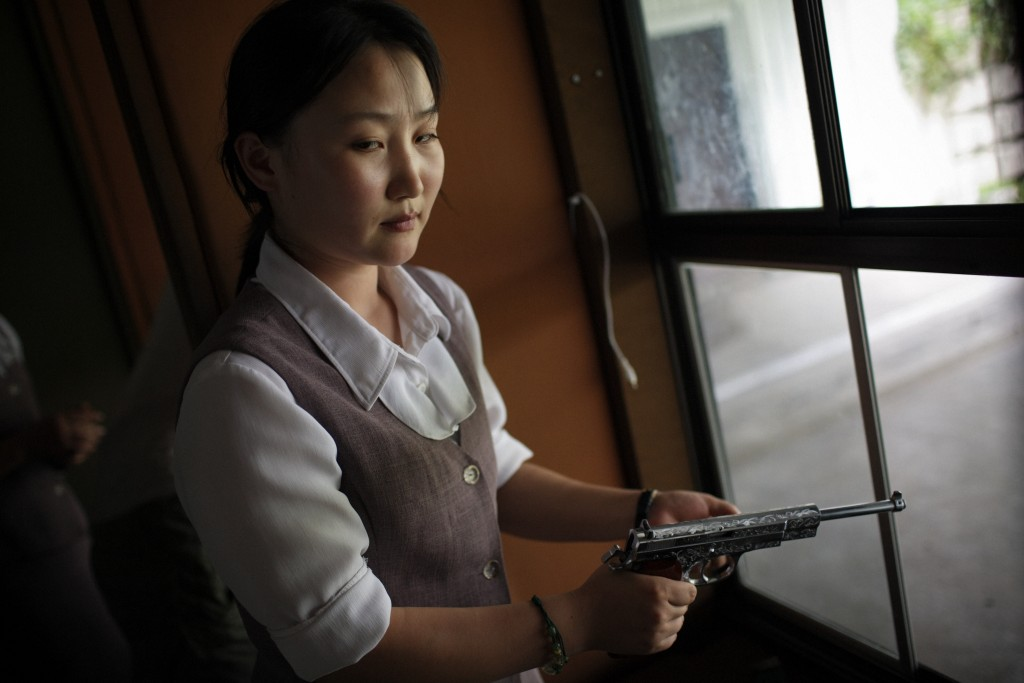 "Thomas van Houtryve. ""A North Korean woman loads a pistol for firing practice in Pyongyang, North Korea,"" 2007."