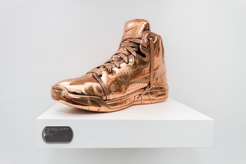 "Kendell Carter. ""WE,"" 2012-2015. Bronze-plated shoes, aluminum dog tags, laminate shelves, installation dimensions variable. /Photo: ""on the wall"" at moniquemeloche."
