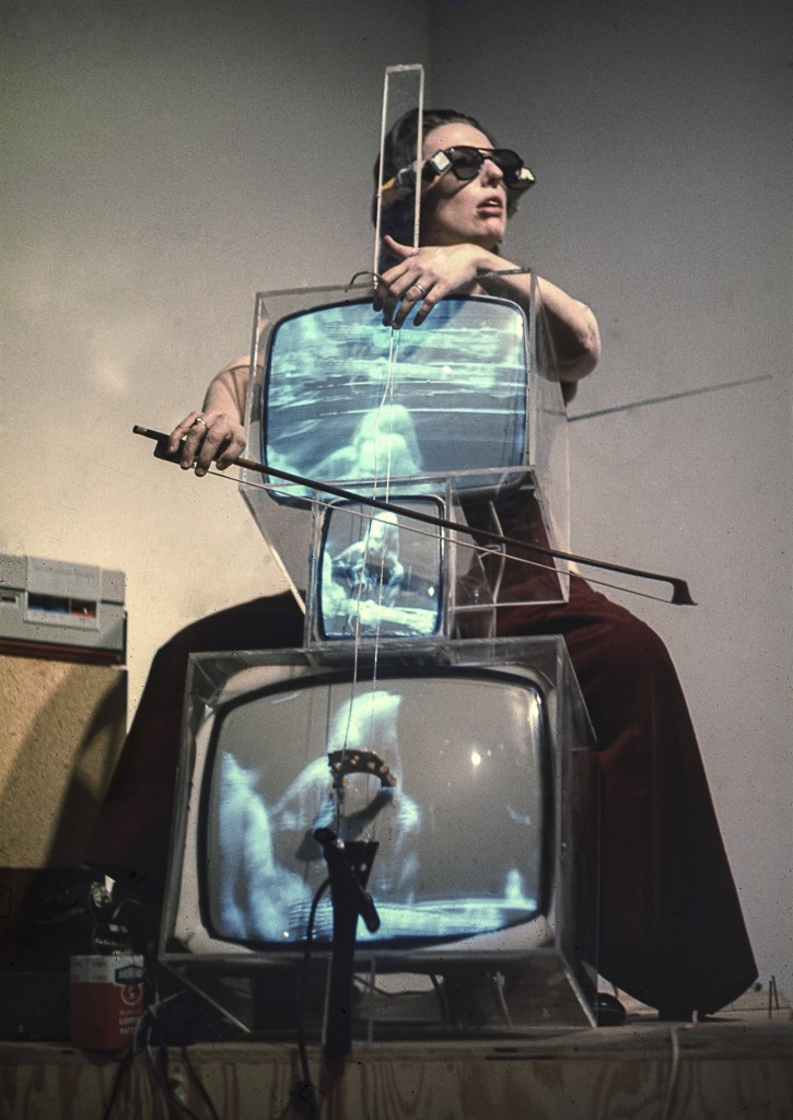 "Charlotte Moorman performs Nam June Paik's ""TV Cello"" wearing ""TV Glasses,"" New York, 1971. /Photo: Takahiko Iimura."