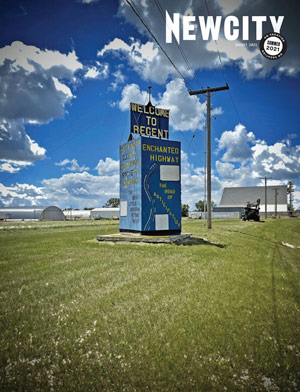 """Newcity August cover showing """"Welcome to Regent"""" sign on lawn grass with blue skies above"""